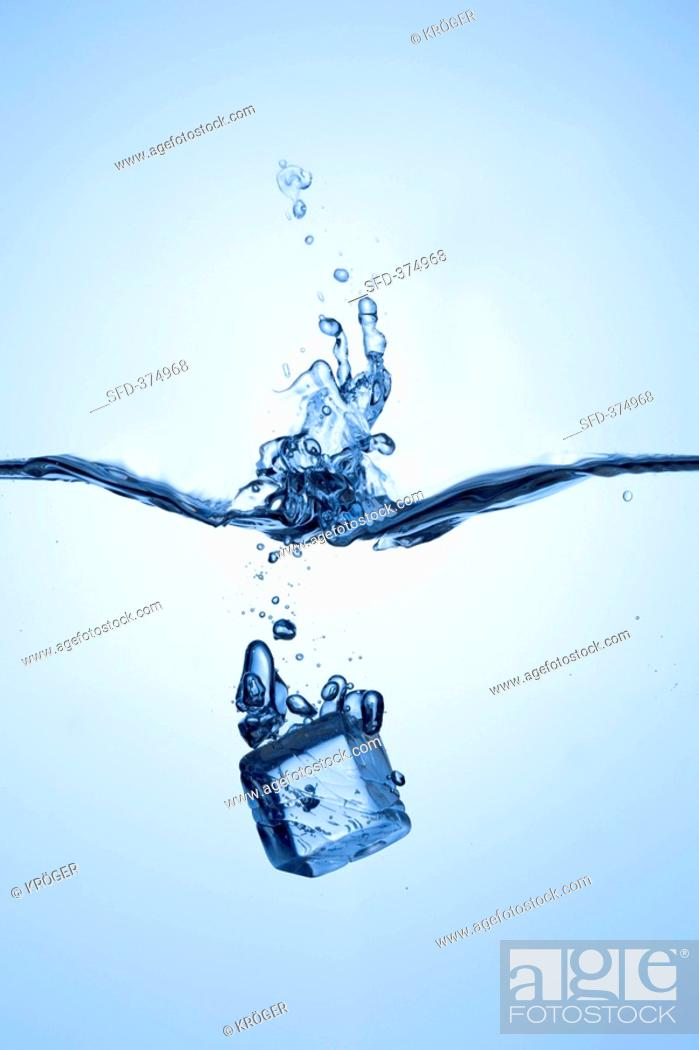 Stock Photo: Ice cube falling into water.