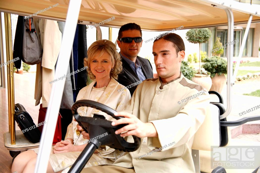 Stock Photo: Couple being driven in cart by hotel bellboy.