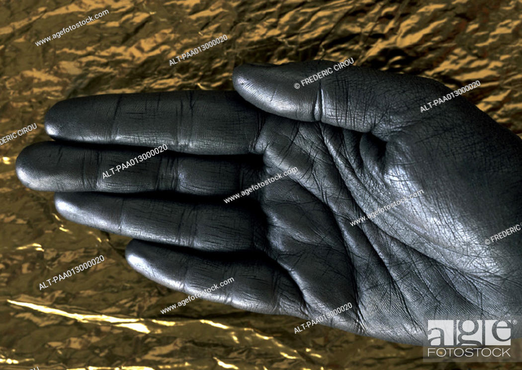 Stock Photo: Silver painted hand against gold paper, close-up.