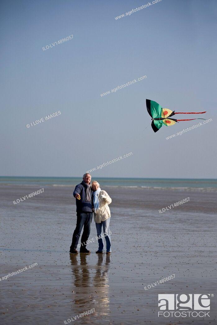 Stock Photo: A senior couple flying a kite on the beach.