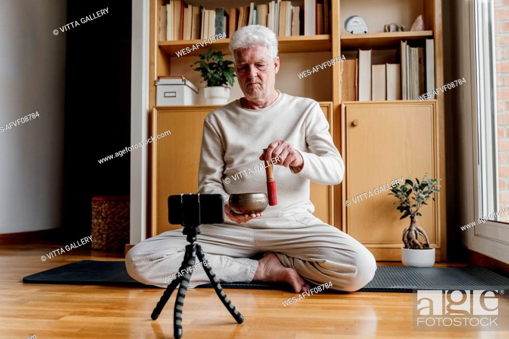 Stock Photo: Male influener showing Tibetan Singing Bowl while vlogging through mobile phone at home.
