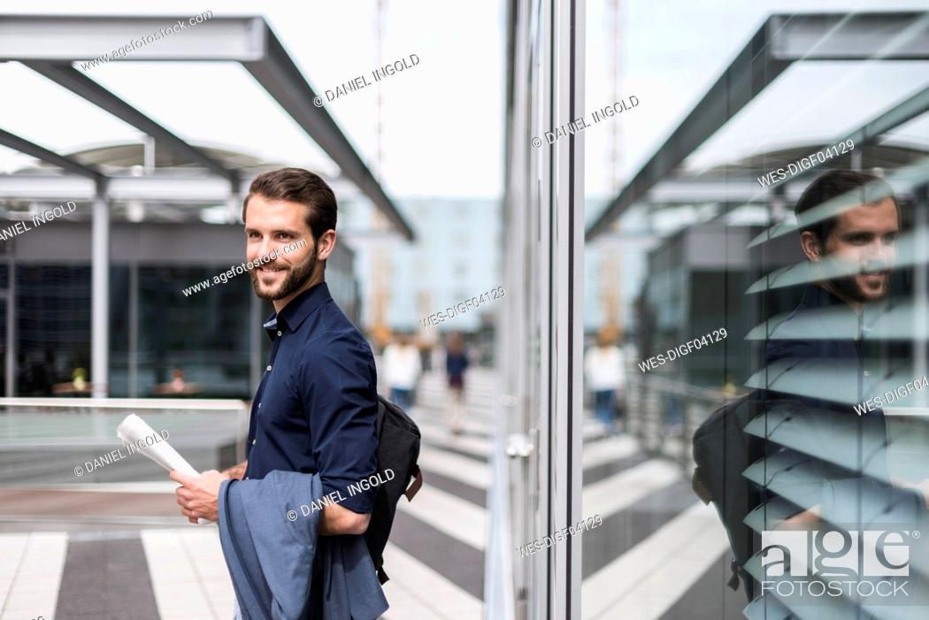Stock Photo: Smiling young businessman standing outdoors holding newspaper.