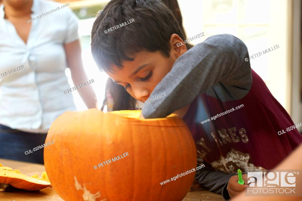 Stock Photo: Mother and children hollowing out pumpkin in dining room.