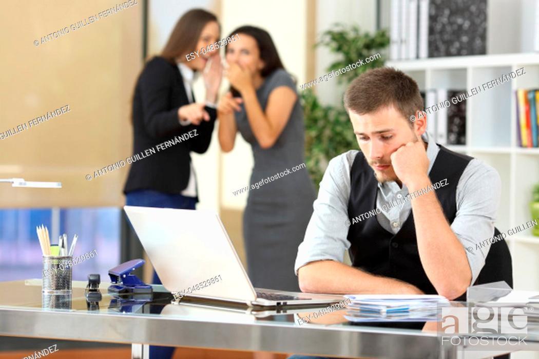 Stock Photo: Two coworkers bullying a worried colleague that is sitting in his workplace at office.
