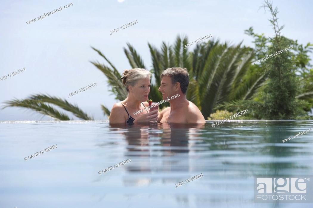Stock Photo: Mature couple drinking daiquiri in outdoor pool.