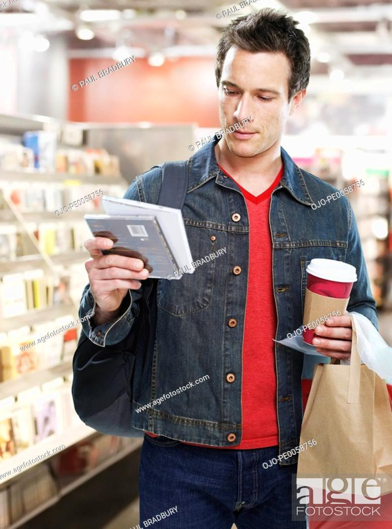 Stock Photo: Man looking at CDs in store.
