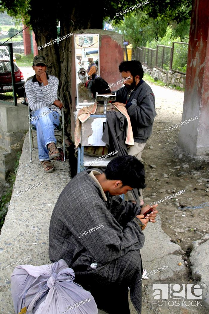 Stock Photo: INDIA, PAHALGAM, 28.06.2010, A Kashmiri roadside barber gives a customer a shave under a tree as two men wait their turns.