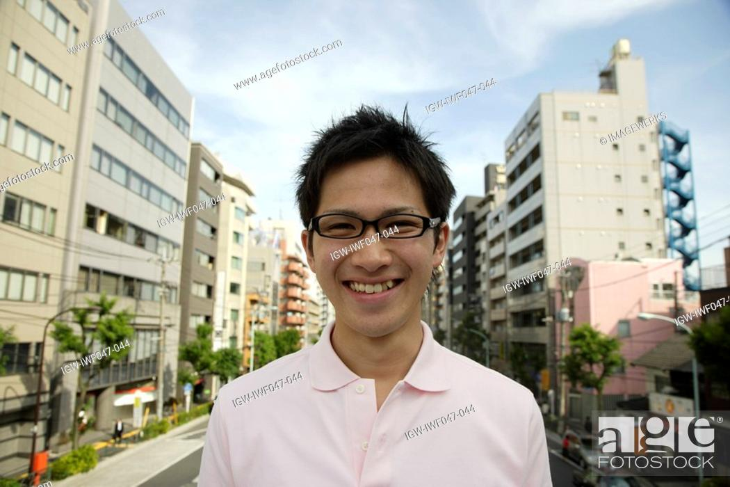 Stock Photo: Portrait of a young man smiling with buildings in background.
