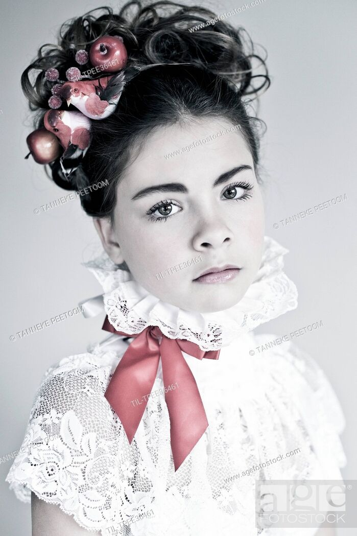 Stock Photo: Female youth with dark curly hair wearing a white lace top with red ribbon and birds.
