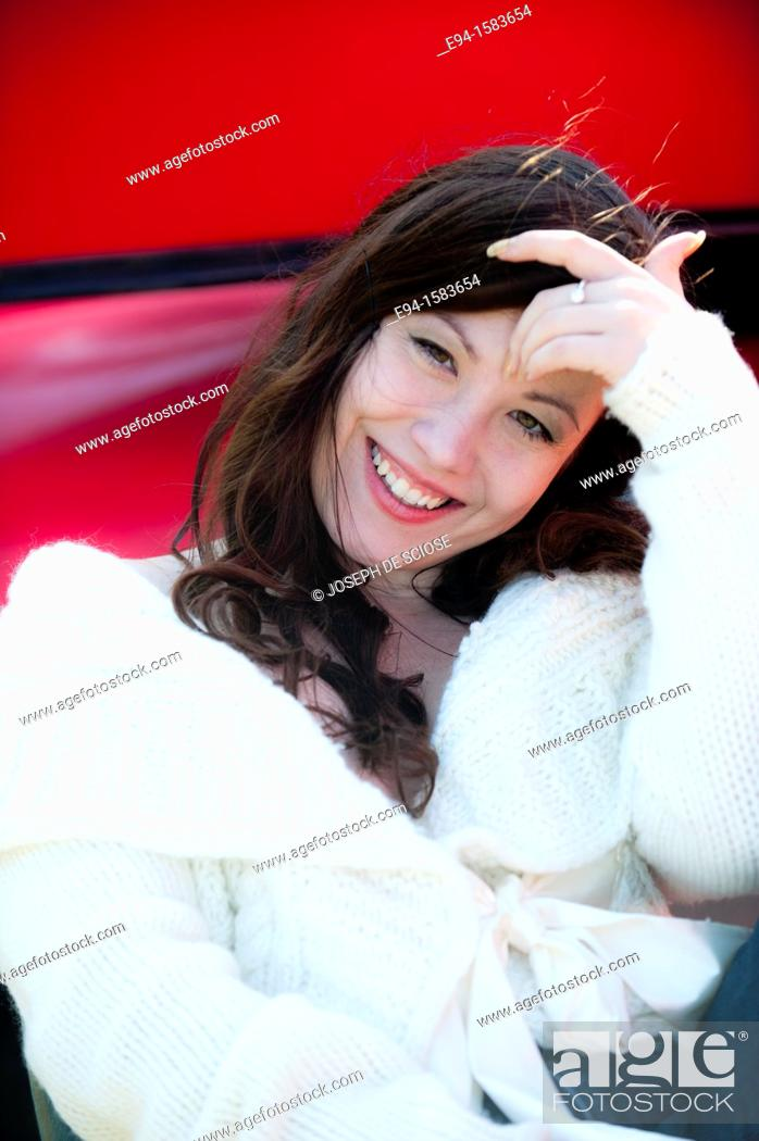 Stock Photo: Portrait of a smiling 25 year old brunette woman wearing a white sweater outdoors.