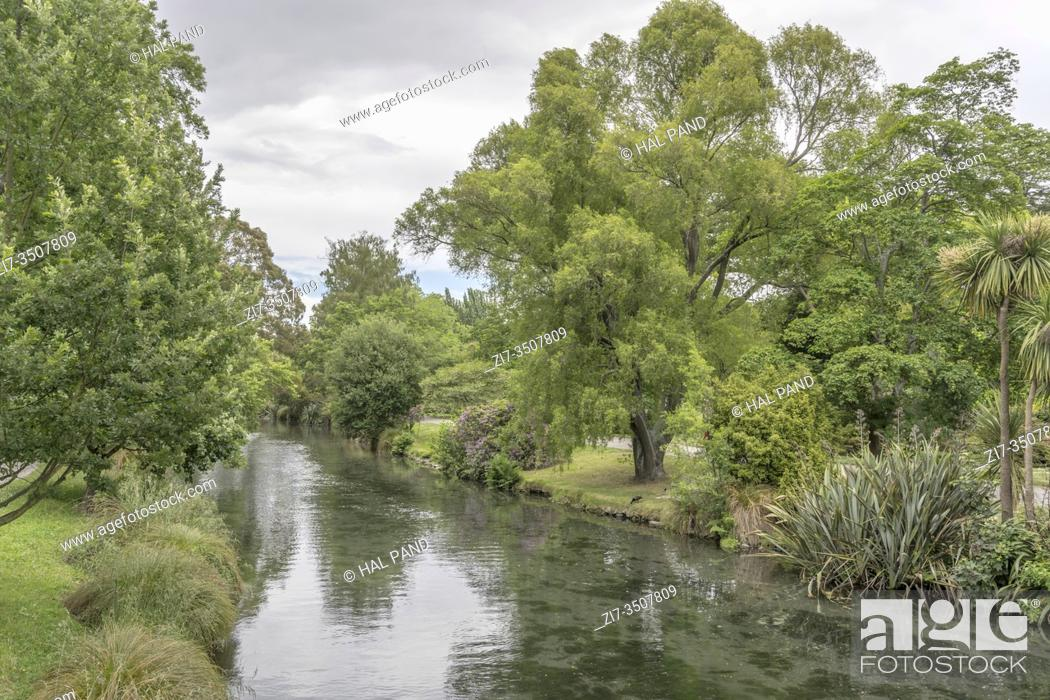 Stock Photo: cityscape with lush vegetation on shores reflecting on Avon river waters at Botanic Gardens, shot in bright spring light at Christchurch, South Island.