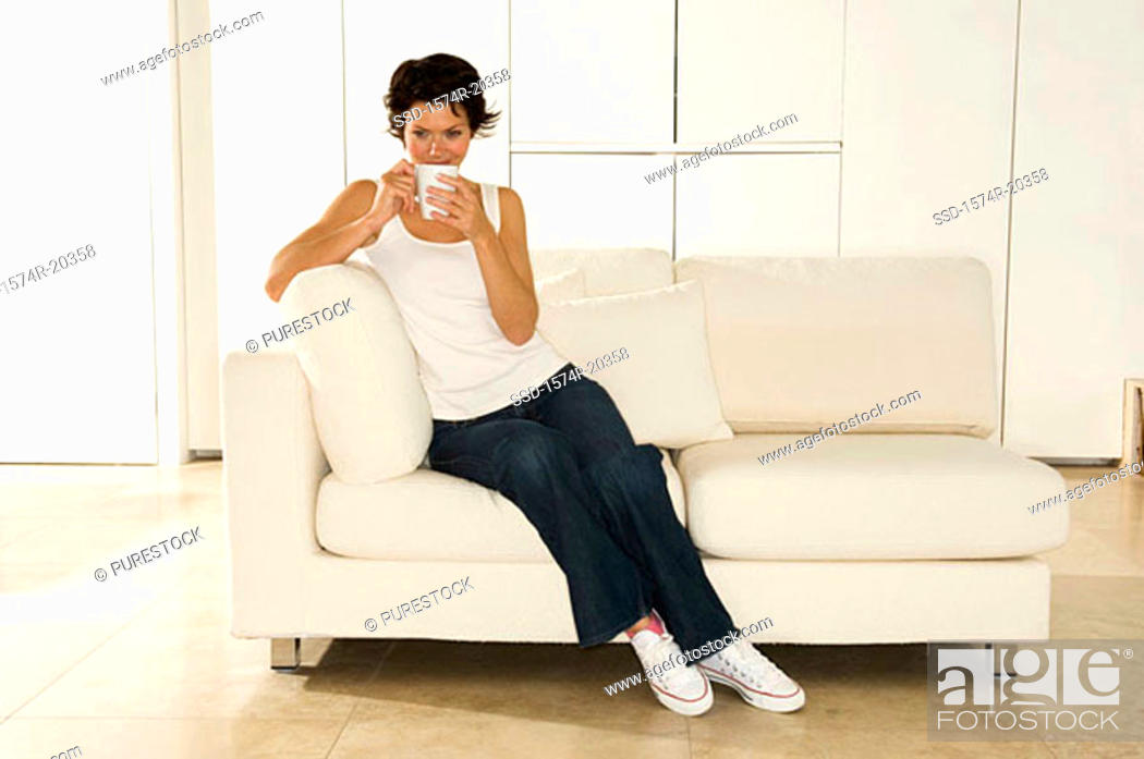 Stock Photo: Young woman sitting on a couch with a cup.
