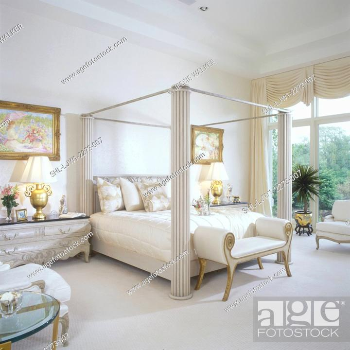stock photo master bedroom elegant modern four poster bed beige tones through out wall to wall carpeting large windows elaborate swag drapes