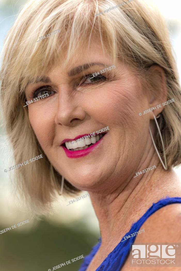 Stock Photo: A portrait of a 60 year old blond woman looking at the camera, outdoors.
