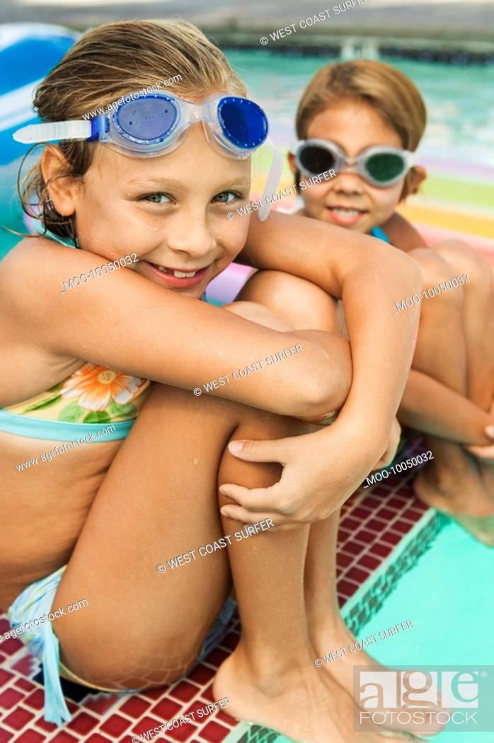 Stock Photo: Two girls 7-9 sitting on edge of swimming pool portrait.