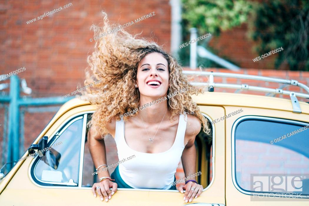 Stock Photo: Portrait of blond woman leaning out of window of classic car tossing her hair.