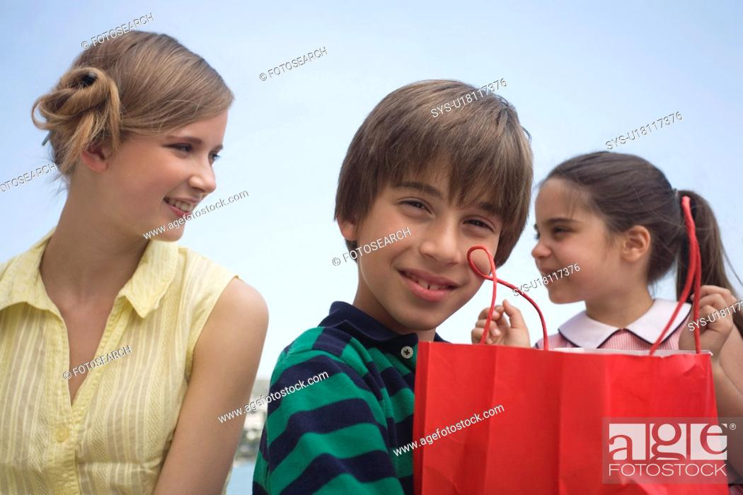 Stock Photo: Mother and two children with shopping bag.