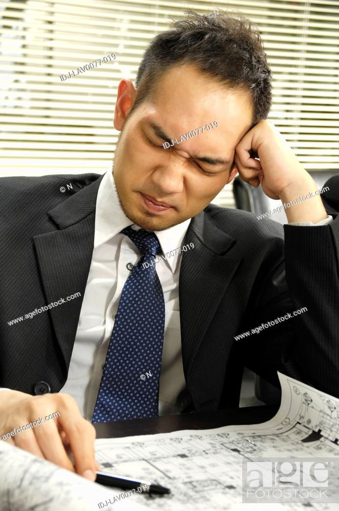 Stock Photo: Architect working on a blueprint and looking frustrated.