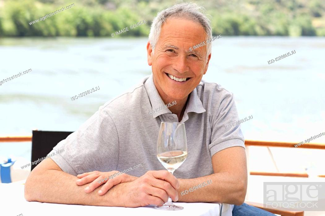 Stock Photo: Senior man with a glass of wine on a boat holiday.