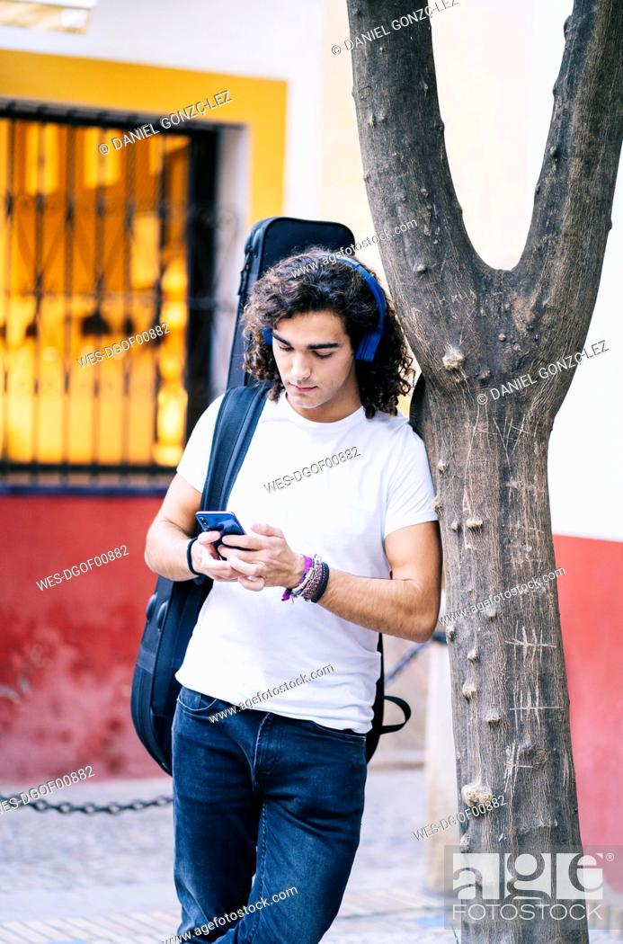 Imagen: Young man using mobile phone while carrying guitar bag, Santa Cruz, Seville, Spain.