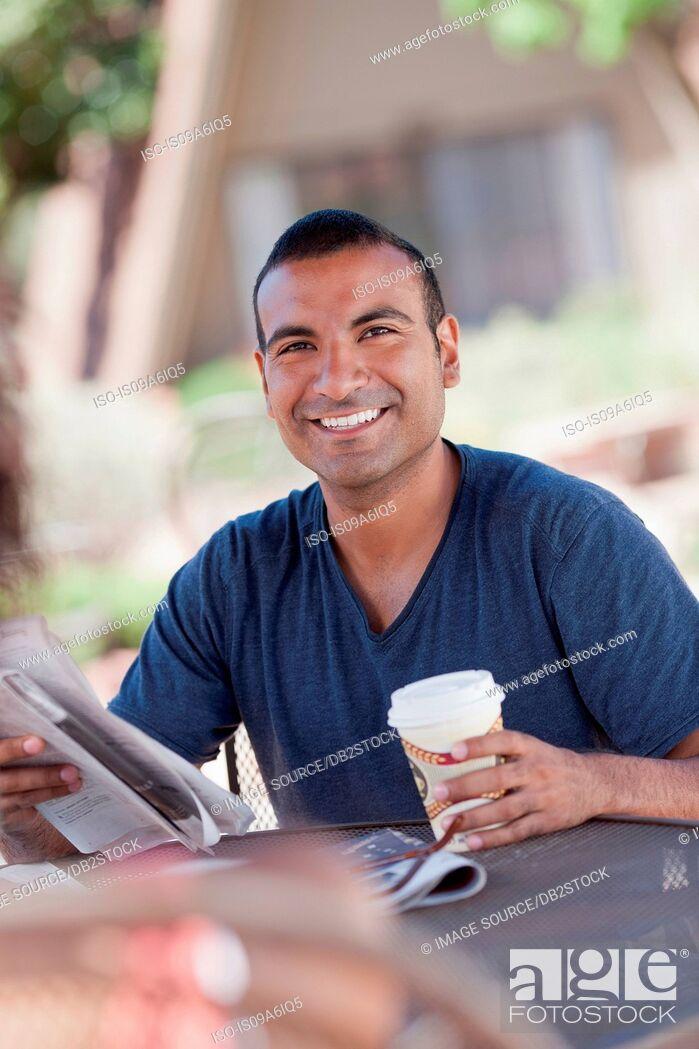 Stock Photo: Man reading newspaper outdoors.