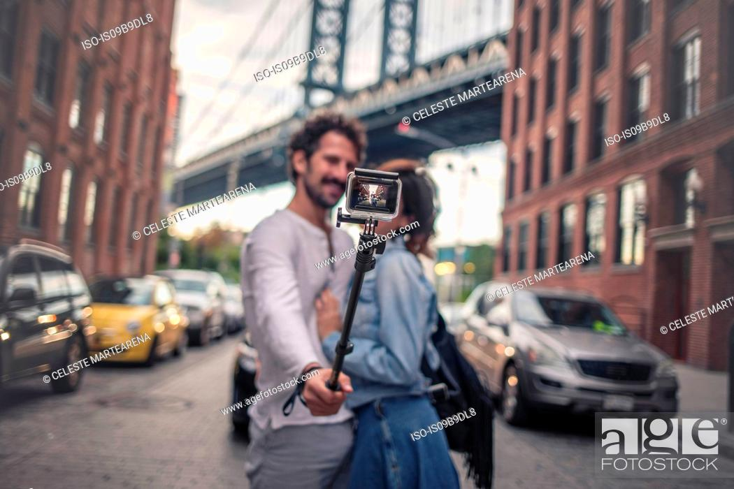 Stock Photo: Couple taking photo with selfie stick, Brooklyn, New York, US.