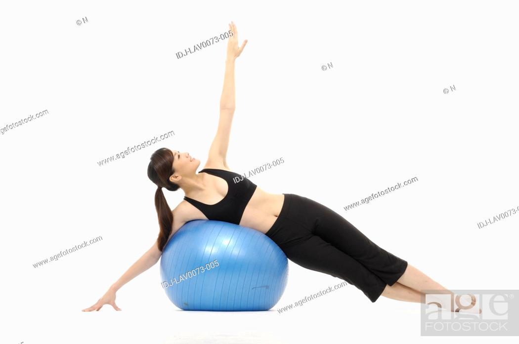Stock Photo: Young woman doing yoga with a fitness ball.