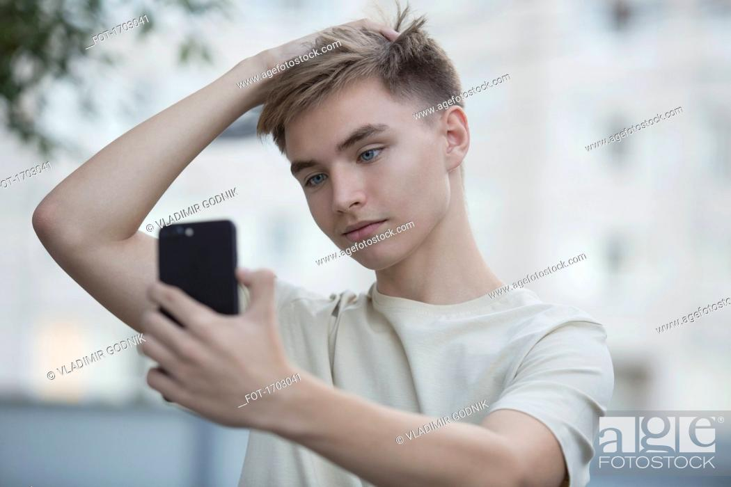 Stock Photo: Teenage boy taking selfie from mobile phone with hand in hair.