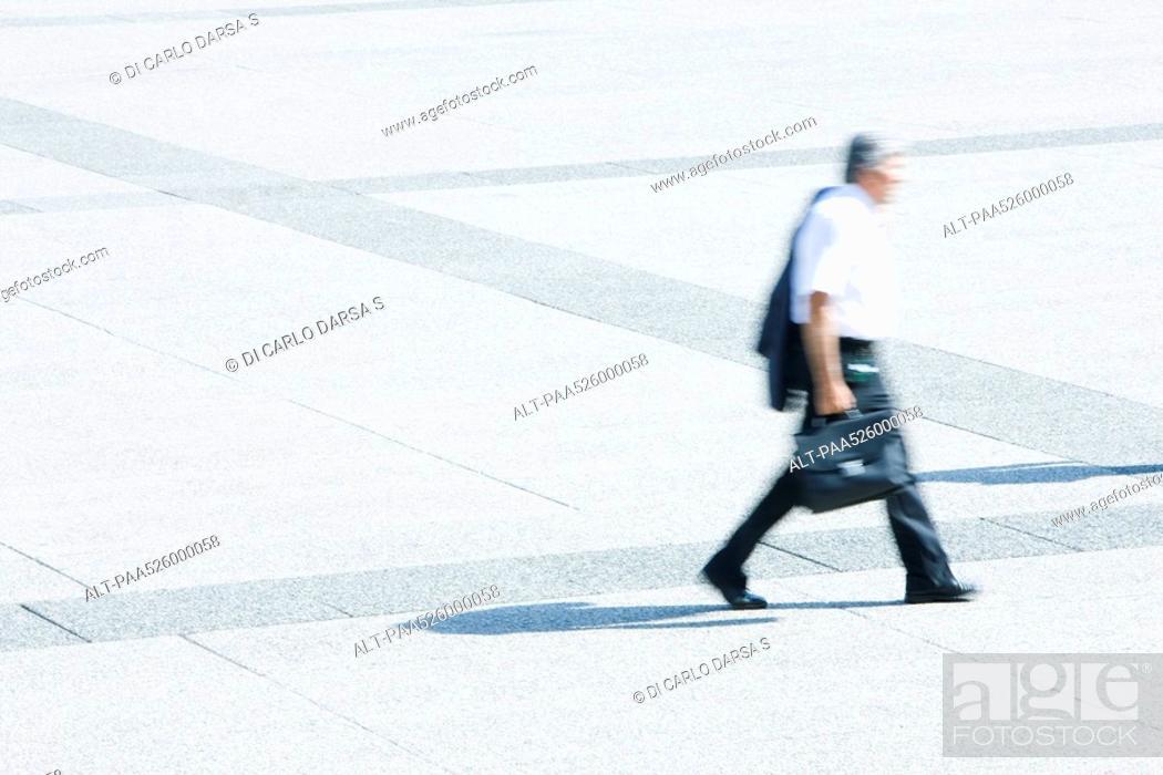 Stock Photo: Businessman with jacket on shoulder walking across public square.