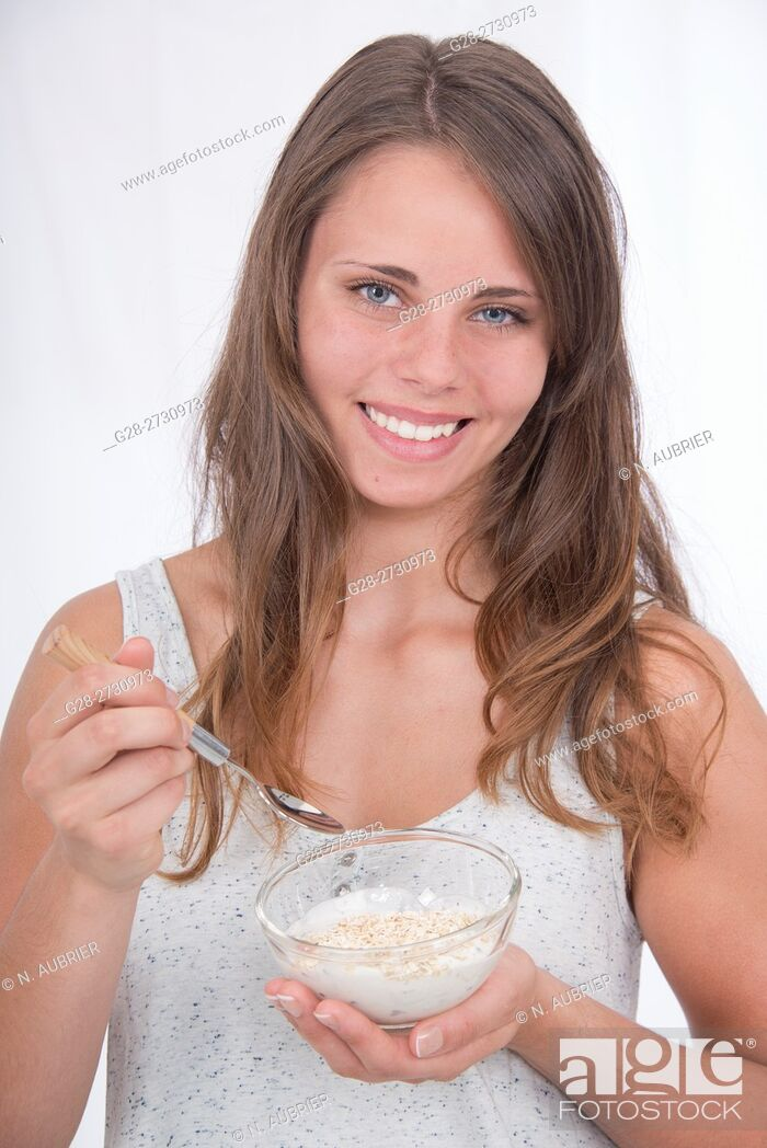 Stock Photo: Beautiful young woman holding a bowl of cereals and cottage cheese i one hand and a spoon in the other, about to eat breakfast.
