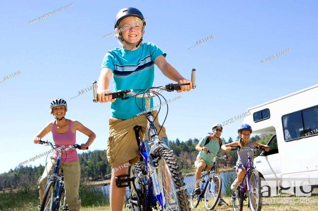 Stock Photo: Family of four on bicycles by motor home, close-up of boy 10-12, low angle view.