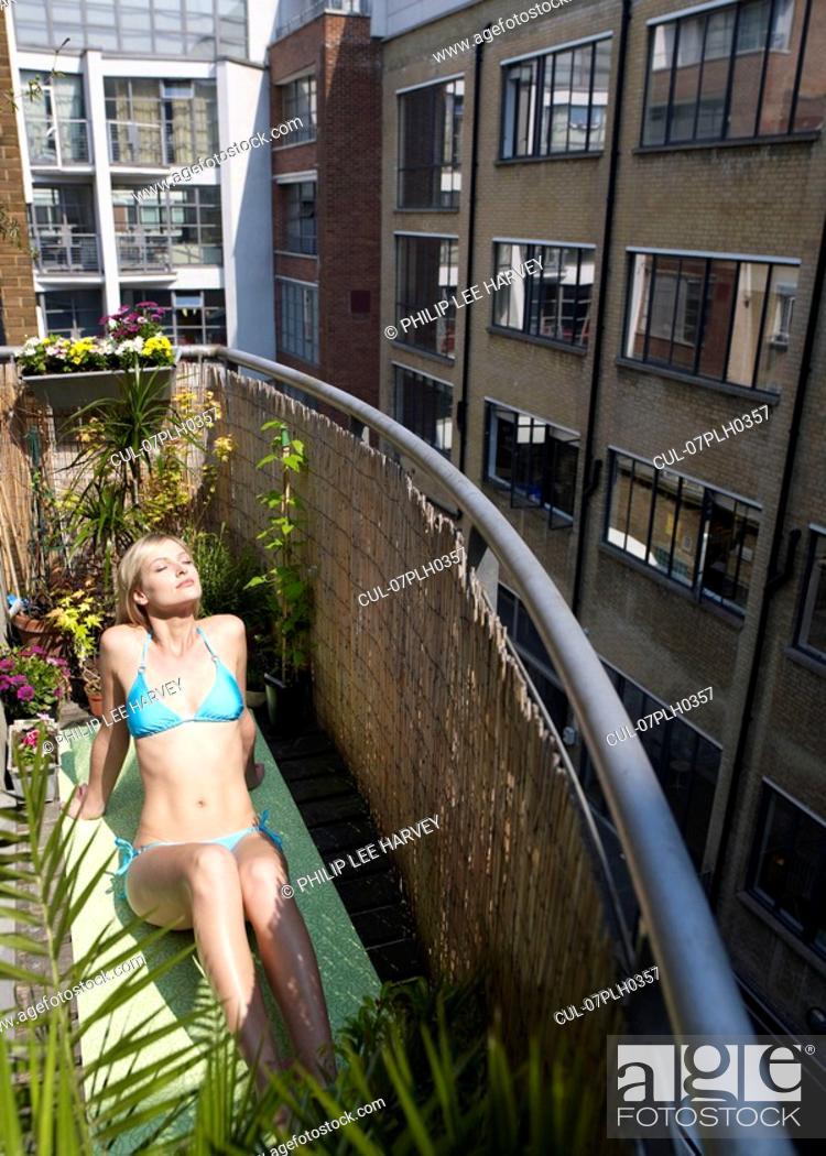 Stock Photo: Woman sunbathing on city balcony.