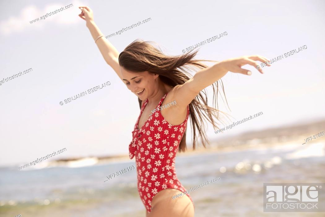 Stock Photo: Young woman touching clouds at beach, in Crete, Greece.
