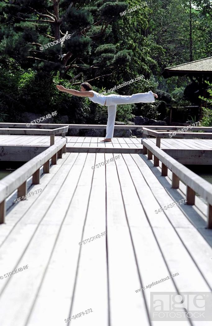 Stock Photo: Woman doing a Yoga-Exercise on a wooden Footbridge - Trees - Nature - Harmony.