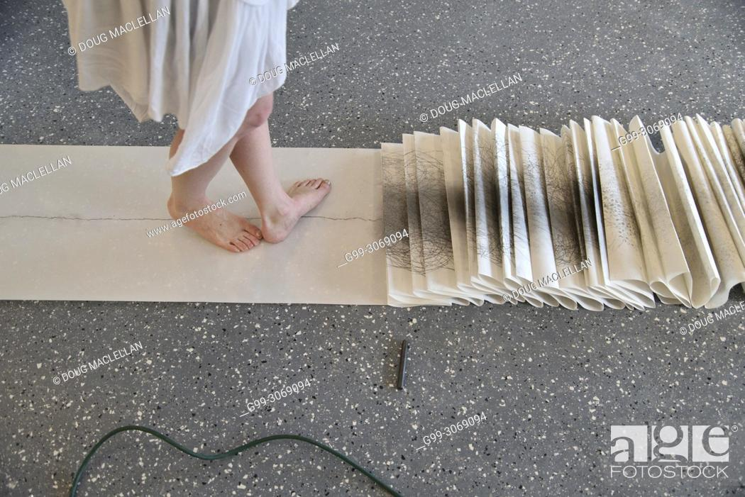Stock Photo: A side view from the knees down of a woman artist in a white dress turning as she creates a performance art work at an artist run gallery in Windsor, Canada.
