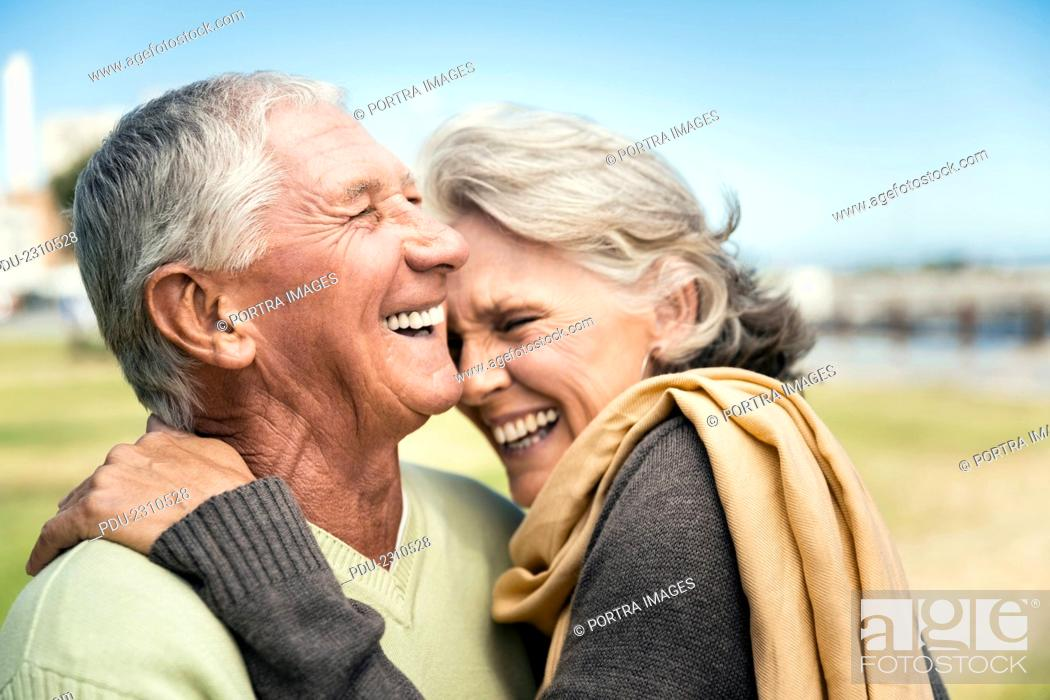 Stock Photo: Side view of happy senior couple embracing in park.