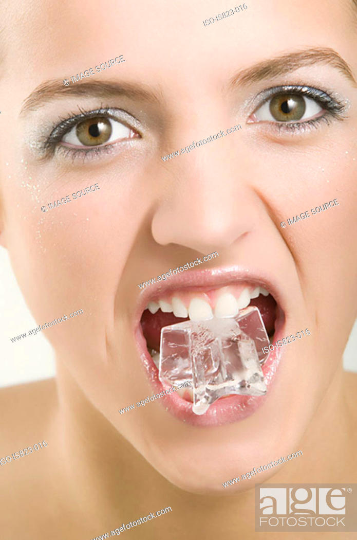 Stock Photo: Woman with an ice cube in her mouth.
