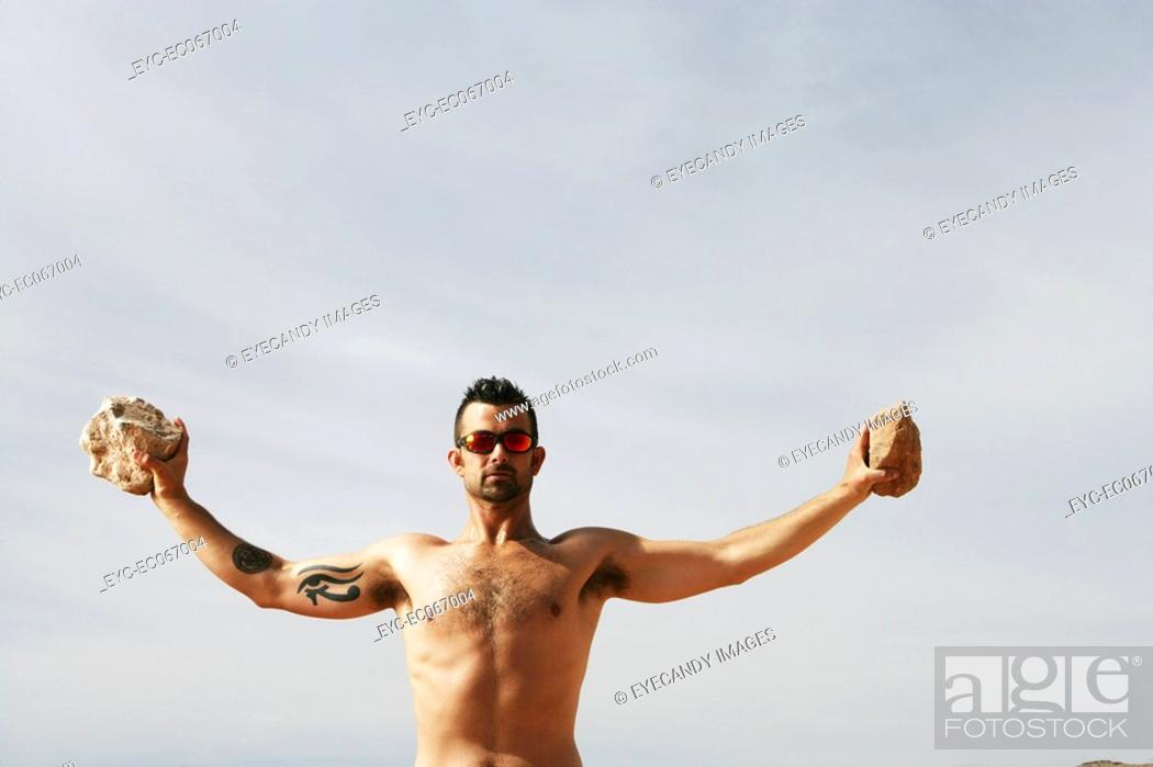 Stock Photo: Caucasian man holding up two rocks during excersice.