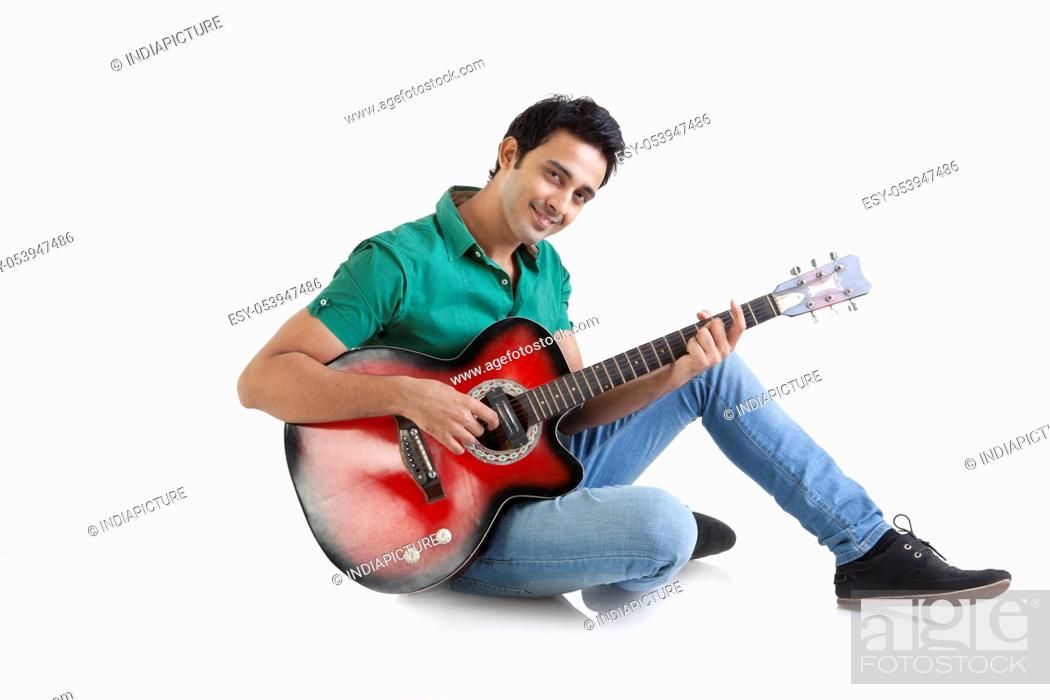 Stock Photo: Portrait of a young man playing a guitar.