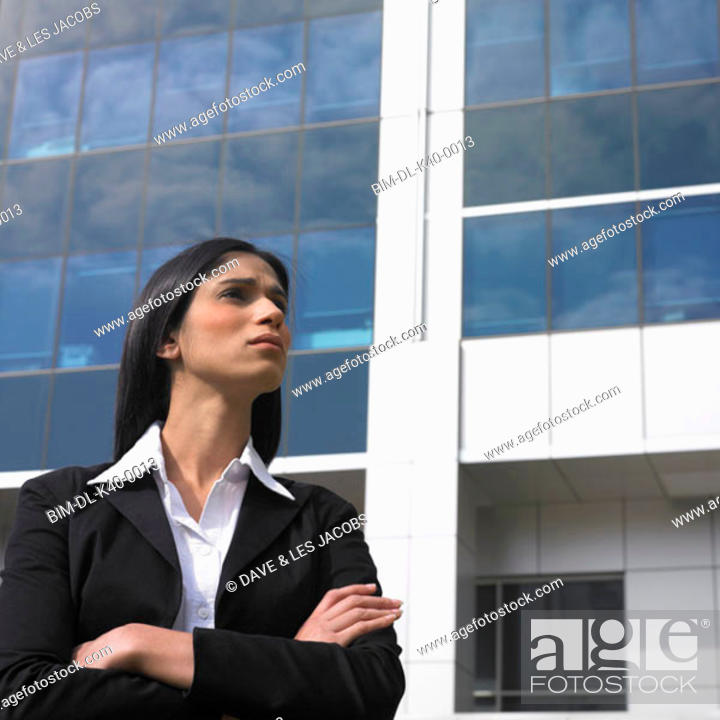 Stock Photo: Young businesswoman standing with arms crossed.
