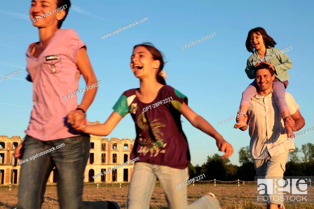 Stock Photo: FAMILY RACING EACH OTHER IN FRONT OF THE RUINS OF THE CHATEAU DE LA FERTE-VIDAME, EURE-ET-LOIR, FRANCE.