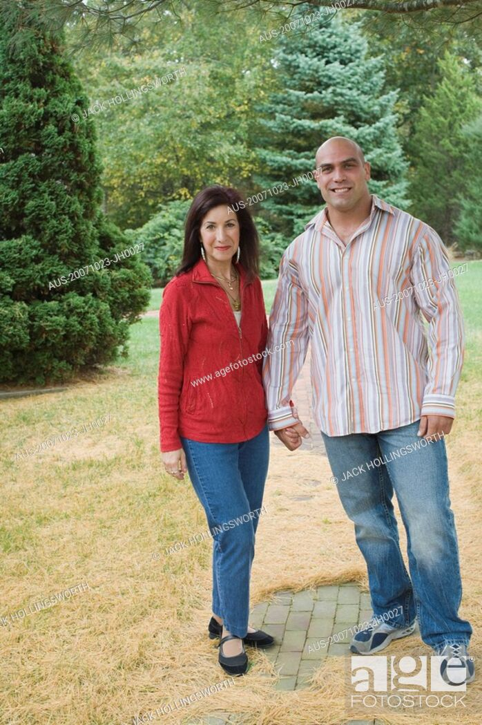 Imagen: Mid adult man standing with a mature woman in a lawn and smiling.