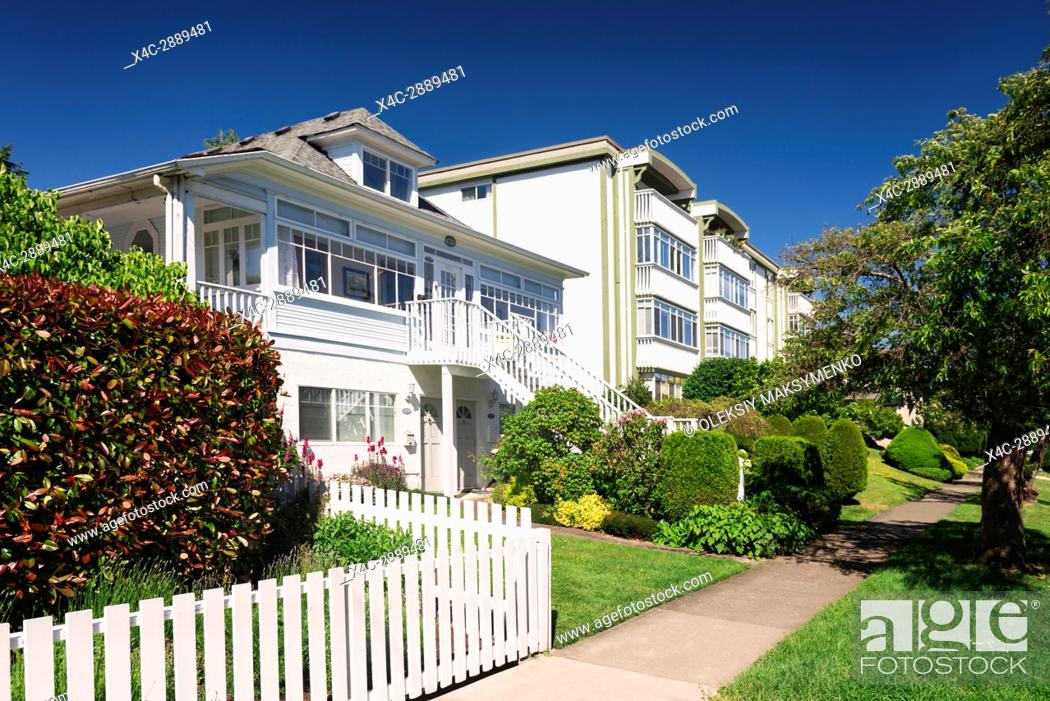 Stock Photo: Beautiful triplex house and an apartment building on a green street in Victoria, BC on a sunny summer day. Victoria, Vancouver Island, British Columbia.