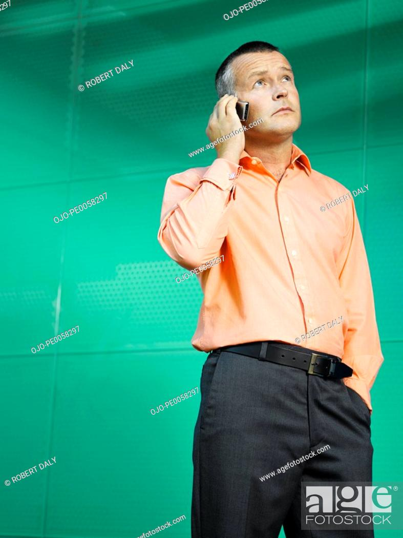 Stock Photo: Businessman on mobile phone in green office.