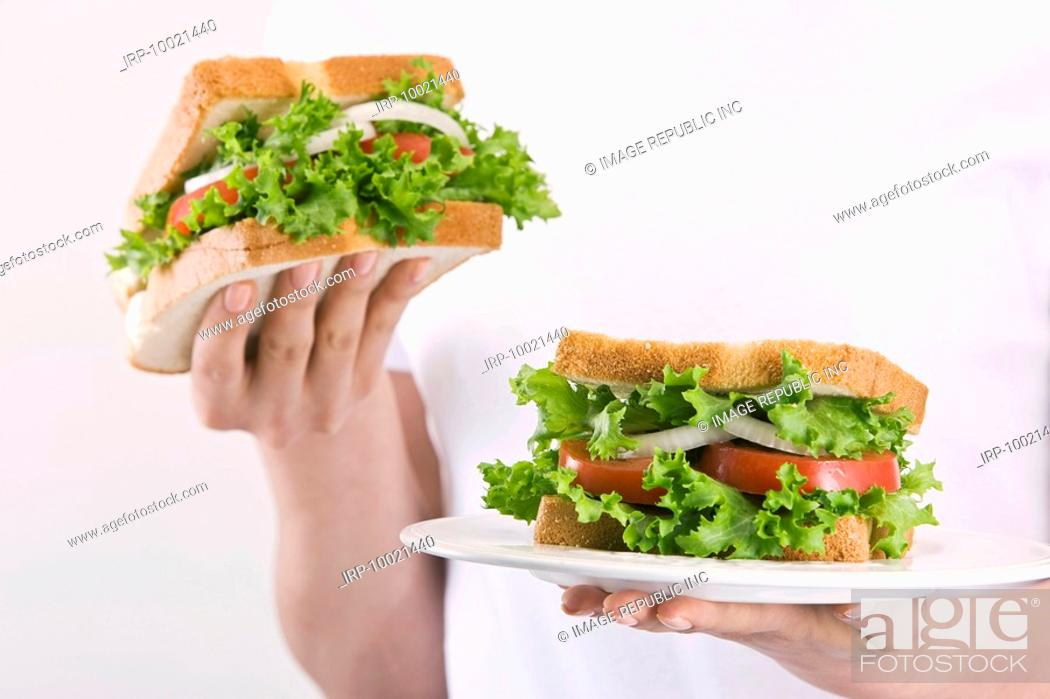 Stock Photo: Woman holding sandwich, close-up, mid section.