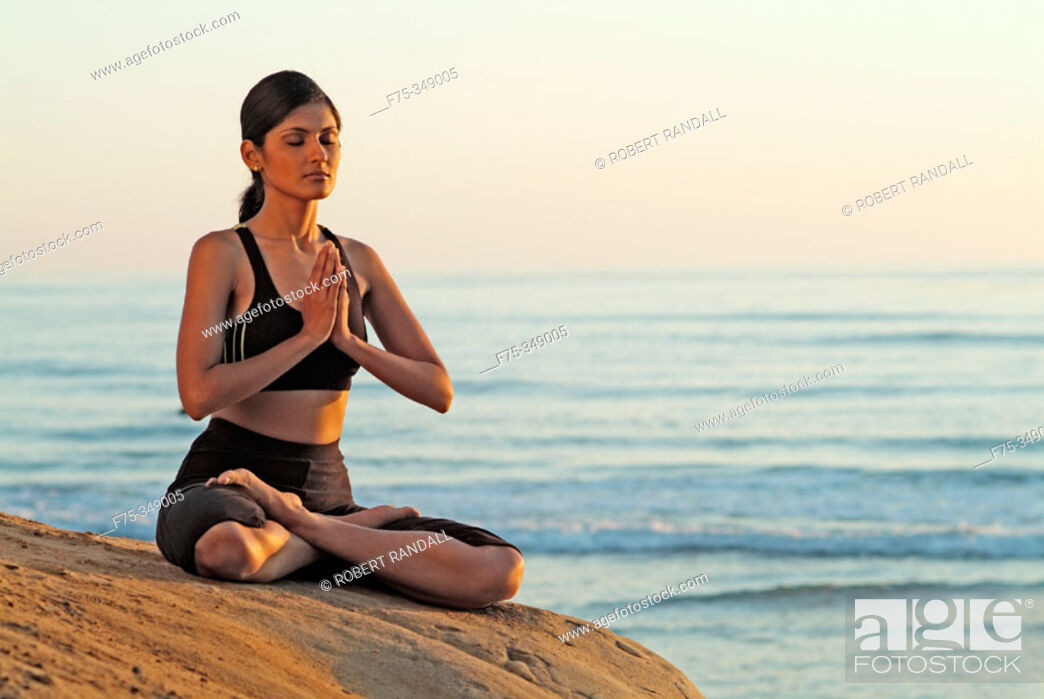 Stock Photo: Indian girl meditating on beach in Carlsbad. California, USA.