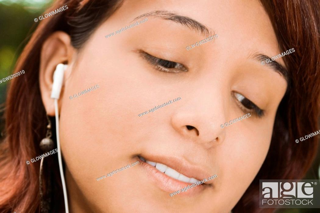 Stock Photo: Close-up of a young woman listening to music.