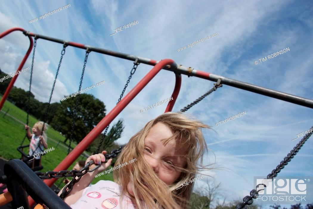 Stock Photo: 5 year girl playing on swing in childrens playground, happy expression.