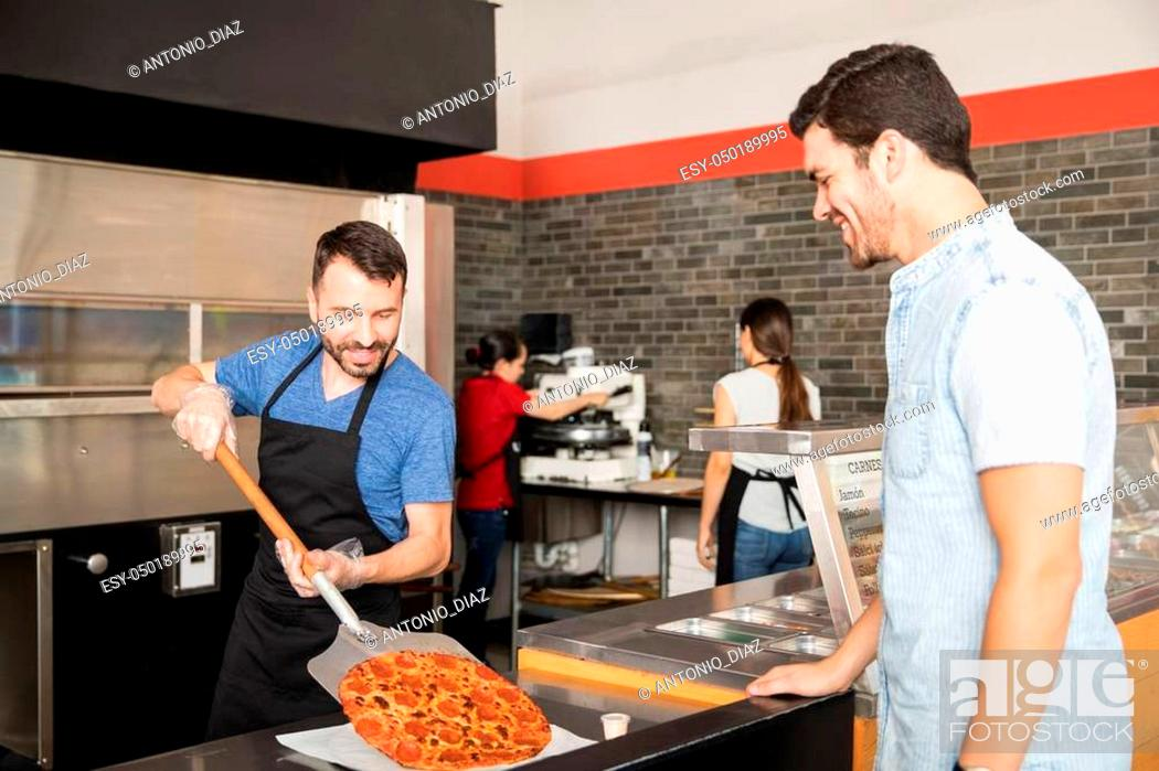 Stock Photo: Handsome man smiling looking at freshly baked pizza order which is being put on serving plate by chef using a peel in restaurant kitchen counter.