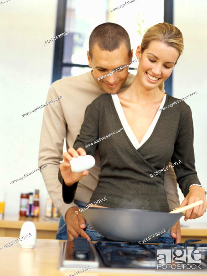 Stock Photo: young woman cooking food with a young man embracing her from behind in the kitchen.